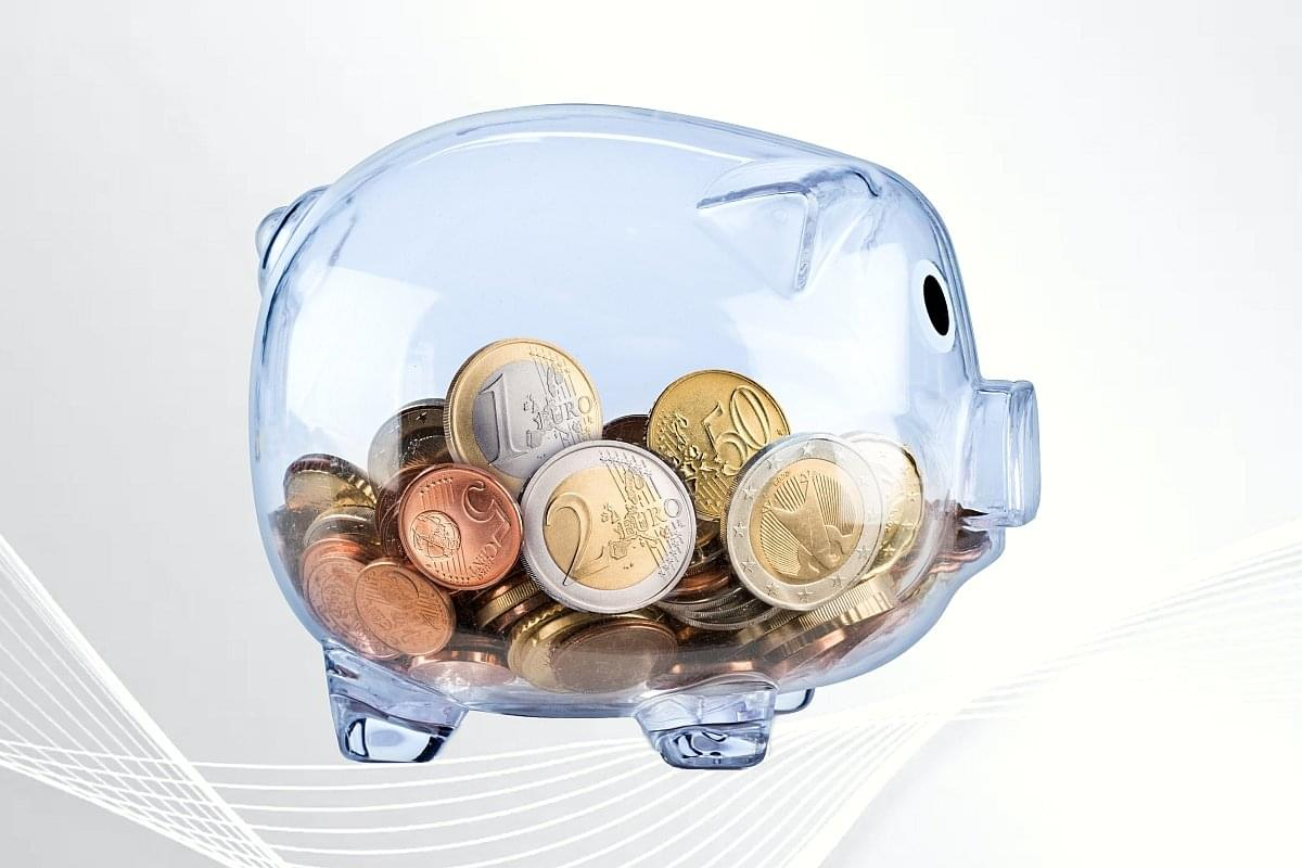 Transparent piggy bank with coins on light gray background